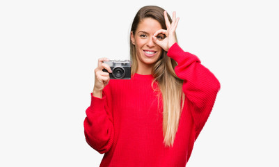 Beautiful young woman holding vintage camera with happy face smiling doing ok sign with hand on eye looking through fingers
