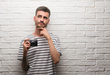Young man holding vintage camera standing over white brick wall serious face thinking about question, very confused idea