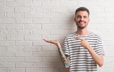 Young adult man standing over white brick wall very happy pointing with hand and finger