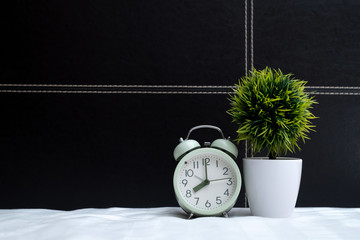 Vintage alarm clock and little decoration tree in white vase on the bed in bedroom at home, wake up or bed time concept.