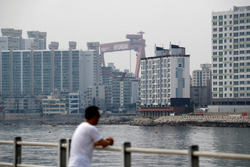 A giant crane of Hyundai Heavy Industries is seen behind apartment complexes in Ulsan