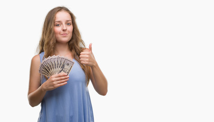 Young blonde woman holding dollars happy with big smile doing ok sign, thumb up with fingers, excellent sign
