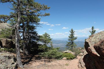 View of mountains in distance on a hike through trees and rock in Colorado