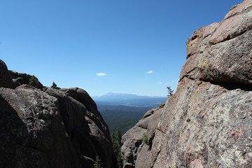 Mountains on horizon looking through large rock structures in Colorado