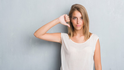 Beautiful young woman standing over grunge grey wall with angry face, negative sign showing dislike with thumbs down, rejection concept