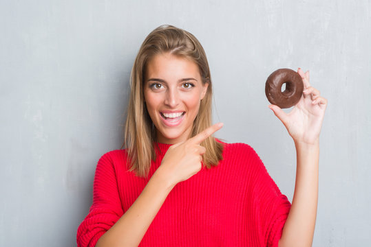 Beautiful young woman over grunge grey wall eating chocolate donut very happy pointing with hand and finger