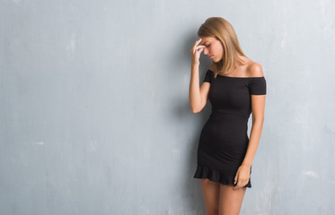Beautiful young woman standing over grunge grey wall wearing elegant dress tired rubbing nose and eyes feeling fatigue and headache. Stress and frustration concept.