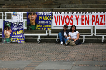 "Relatives of one of the soldiers kidnapped by the rebels of the Marxist National Liberation Army (ELN) of Colombia, sit outside the Congress building of the Republic with signs that reads ""alive and in peace"" in Bogota"