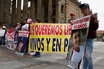 Relatives of one of the soldiers kidnapped by the rebels of the Marxist National Liberation Army (ELN) of Colombia, hold pictures and signs outside of the Congress building of the Republic in Bogota, Colombia