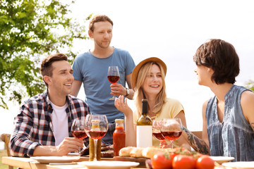 Young people with glasses of wine at table outdoors. Summer barbecue