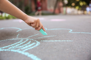 Little child drawing with chalk on asphalt, closeup