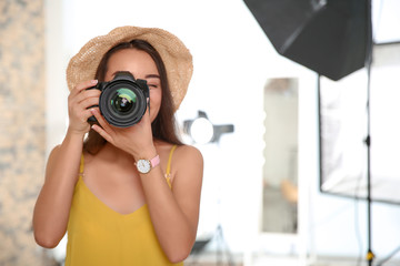 Professional photographer with camera in photo studio