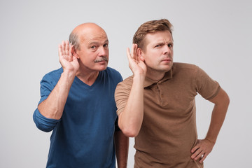 Two caucasian men hearing with hand on ear isolated on a white background. Please speak loudly.