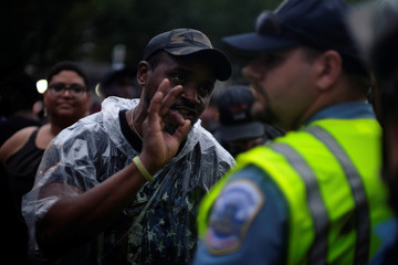 An anti-fascist counter-protester gestures toward police officers guarding the White House on Pennsylvania Avenue in Washington