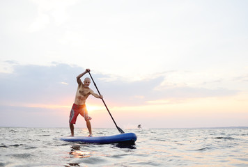 A man stands on a SUP board against the background of the sea and the sunset.