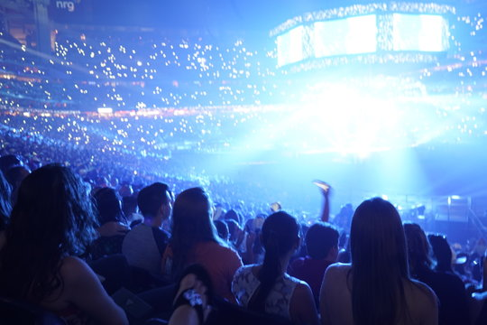 Concert stage with shining lights and crowd at a performance. Rock music event at a stadium with colorful spotlights and projectors.