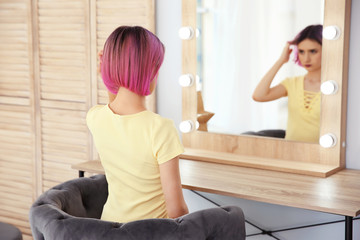 Young woman with color hair looking into mirror in beauty salon. Modern trend