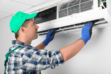 Male technician installing air conditioner indoors