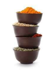 Stack of bowls with different aromatic spices on white background