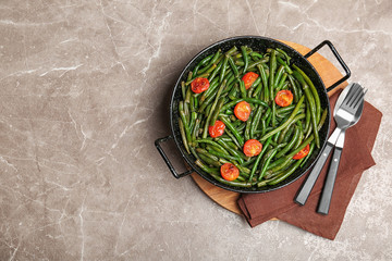 Tasty green beans with cherry tomatoes in serving pan on table, top view