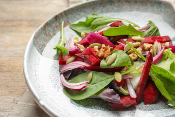 Plate with delicious beet salad on table, closeup