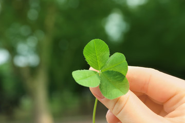 Woman holding four-leaf clover outdoors, closeup with space for text