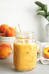 Tasty peach smoothie in mason jar and fresh fruit on table