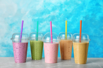 Plastic cups with smoothies on table against color background