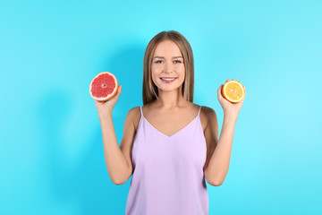 Slim woman with citrus fruits on color background. Healthy diet