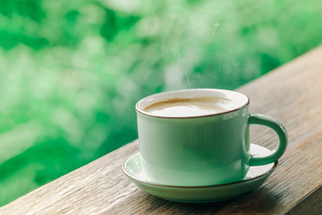 hot coffee cup on natural green background