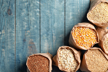 Bags of different cereal grains on wooden background, flat lay composition with space for text