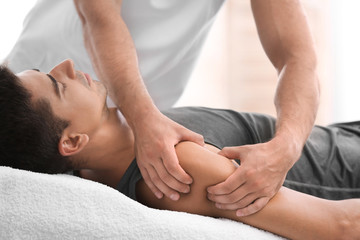 Young man receiving massage in salon, closeup