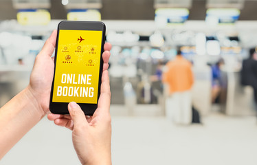 Close up hand holding mobile phone and touch on screen with online booking word with feature icon at check in airport counter blur background,Digital lifestyle Technology concept.
