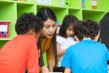 Asian female teacher teaching mixed race kids reading book in classroom,Kindergarten pre school concept.