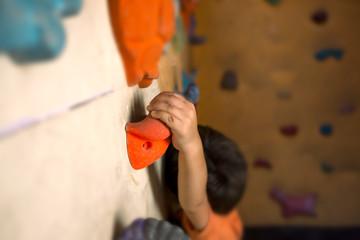 The boy trains on a climbing wall.