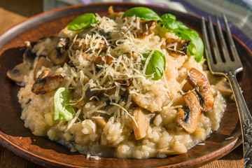 Italian dish - vegetarian mushroom risotto with basil leaves and Parmesan cheese in a clay plate naprostovatom village table