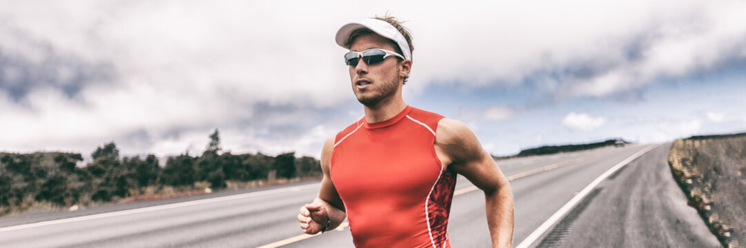 Triathlon runner man running on road panoramic backbround. Fit athlete jogging on competition race. Triathlete training for marathon banner panorama.