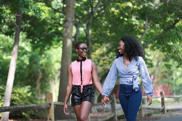Happy black women holding hands while walking
