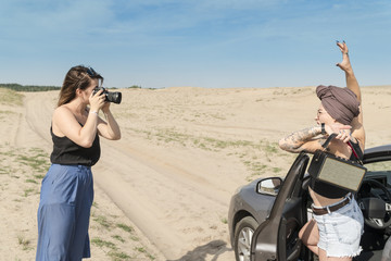 Photographer takes a photo shoot model with loudspeaker at the car in the desert