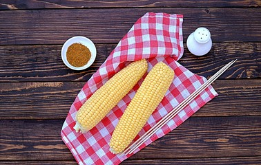 Ingredients for cooking corn grill on a wooden background. Fresh organic corn cobs, wooden skewers, spices, salt. Top view