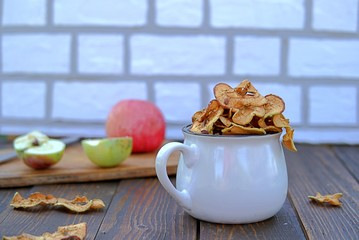 Dried organic apples in a white ceramic cup. Harvest processing of apples.
