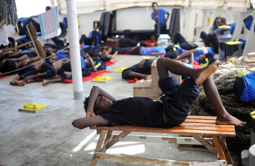 Migrants are seen resting on board of the MV Aquarius rescue ship