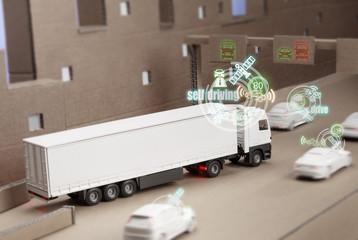Fototapeta Spielzeug LKW auf einer Karton Autobahn simuliert Autonomes ein Spuren in den Verkehr