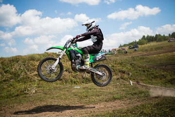 A picture of a biker doing a trick, and jumping into the air. Motocross Championship. sports fast driving. bike large small.