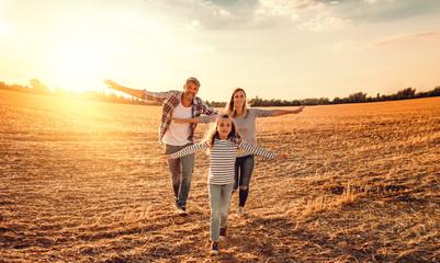 familie mit tochter rennt übers Feld