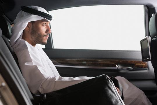 Emirati businessman traveling in car.