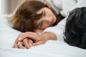 Young couple in love holding hands and looking at each other lying together on white bed Romantic moment
