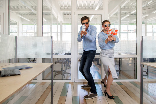 Man and woman in formal outfits standing back to back and aiming toy guns while having fun in office