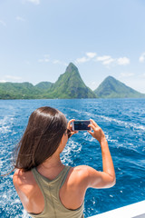 Caribbean travel girl taking photo with phone on St Lucia Pitons boat cruise ride in tropical vacation summer lifestyle.