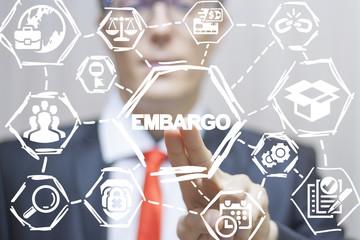 Businessman or politician clicks a embargo text button on a virtual panel. Embargo business finance politics concept. Wall mural